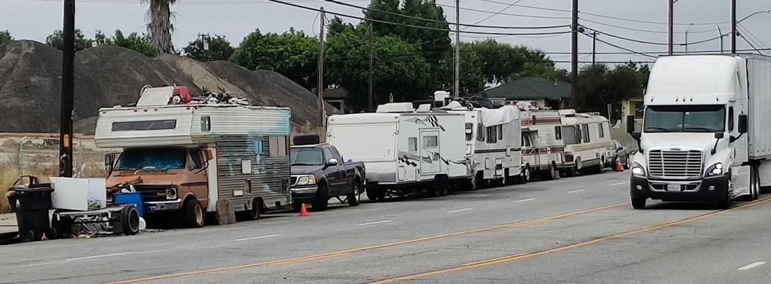 Campers near warehouse with a big rig